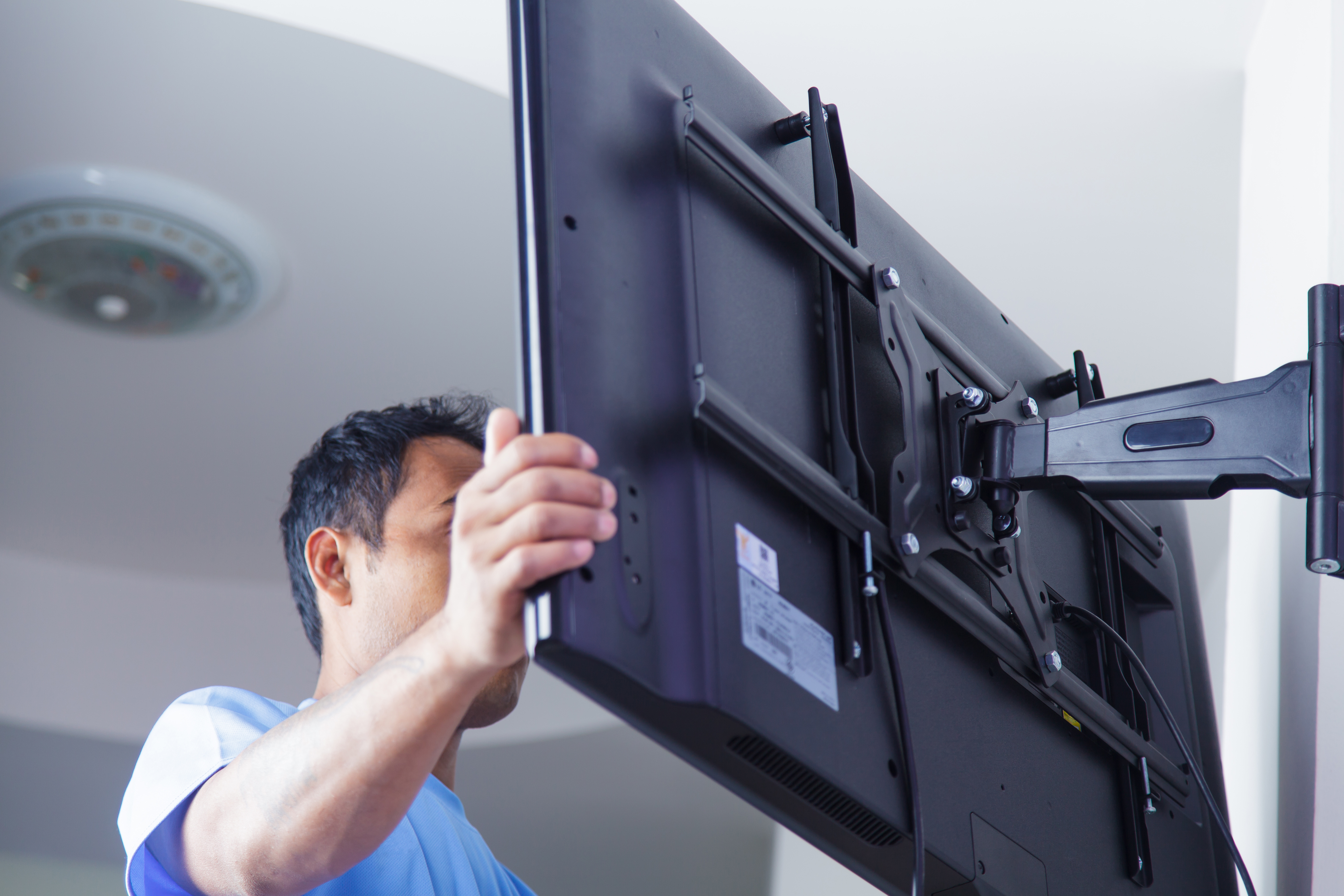 Installer Mounting TV on the wall by using mounting TV brackets