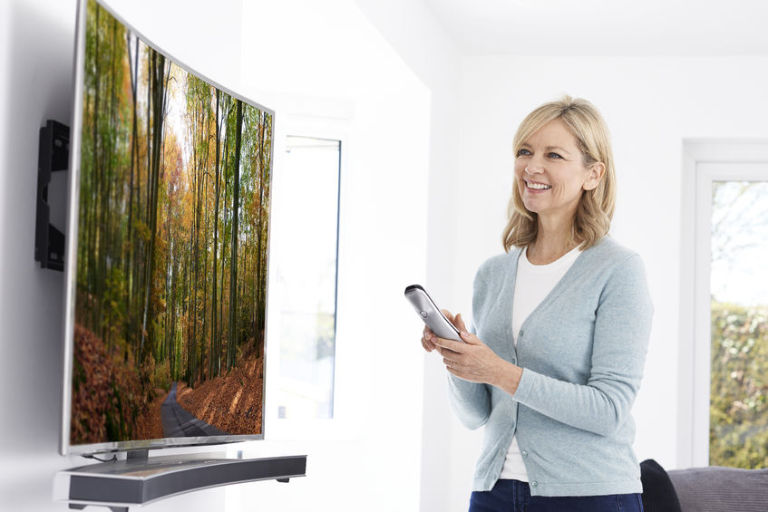Mature Woman With New Curved Screen Television At Home