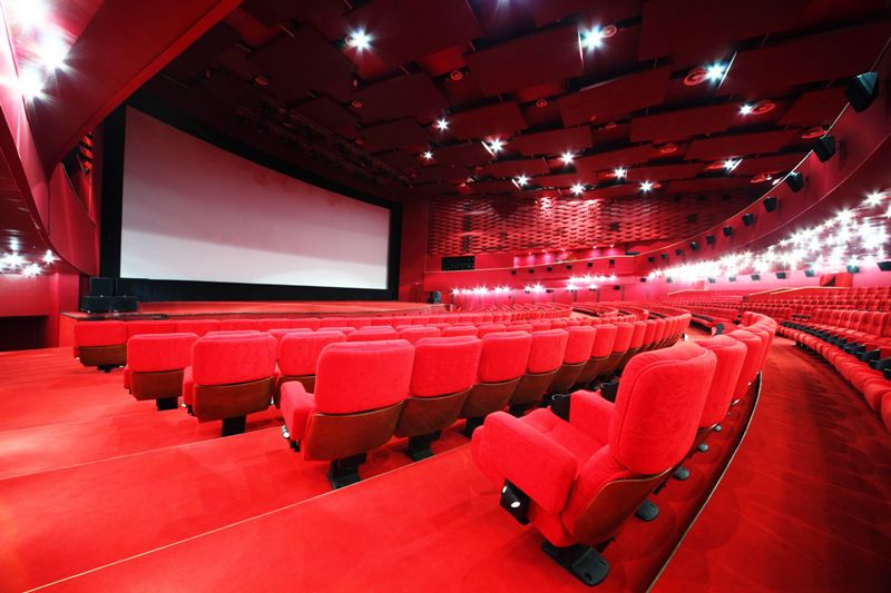 comfortable red chairs in illuminate red room cinema IMAX