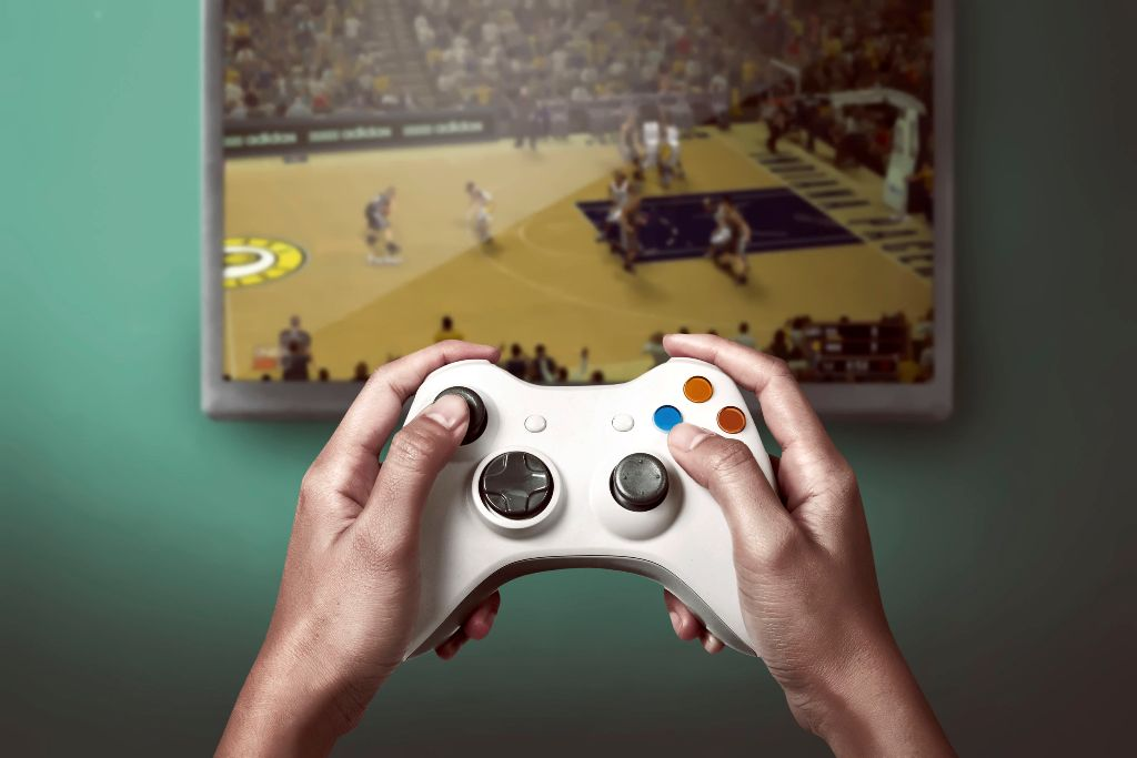 game console controller playing sports game on the television
